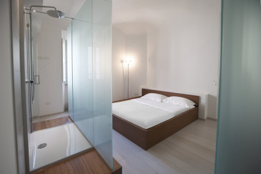 Nella camera Corner la doccia prende posto su un lato della stanza, celata da un grande pannello vetrato satinato.