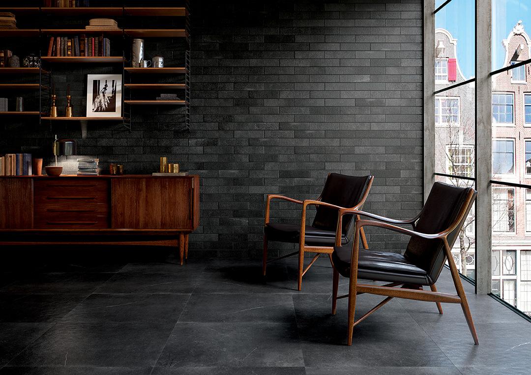 Elegante zona living firmata con la collezione Maku di Fap ceramiche. La parete è realizzata con il rivestimento in grès porcellanato Maku Atelier Dark 7,50x30 cm, mentre il pavimento con la versione Matt di Maku Dark in grès porcellanato, nel formato maxi 75x75 RT cm