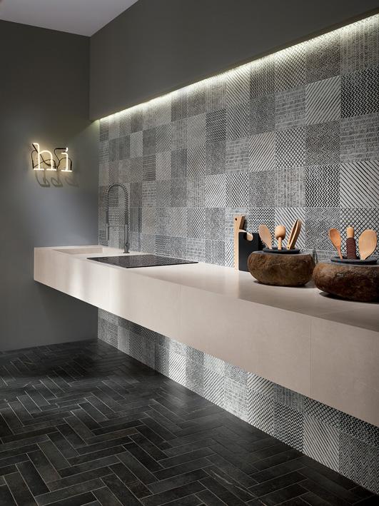 Moderno ambiente cucina firmato con la collezione Maku di Fap ceramiche. La parete è realizzata con il rivestimento in grès porcellanato Maku Déco Light 20x20 cm, che offre una raffinata trama di decorazioni grafiche, mentre il pavimento con la versione Matt di Maku Atelier Dark in grès porcellanato nel formato 7,5x30 cm