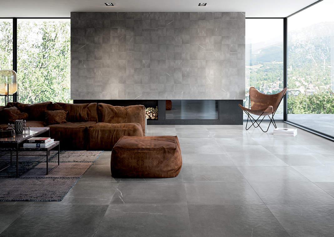 Elegante zona living firmata con la collezione Maku di Fap ceramiche. La parete del camino è realizzata con il rivestimento in grès porcellanato Maku Atelier Grey 20x20 cm, mentre il pavimento con la versione Satin di Maku Grey in grès porcellanato, nel formato maxi 75x75 RT cm.