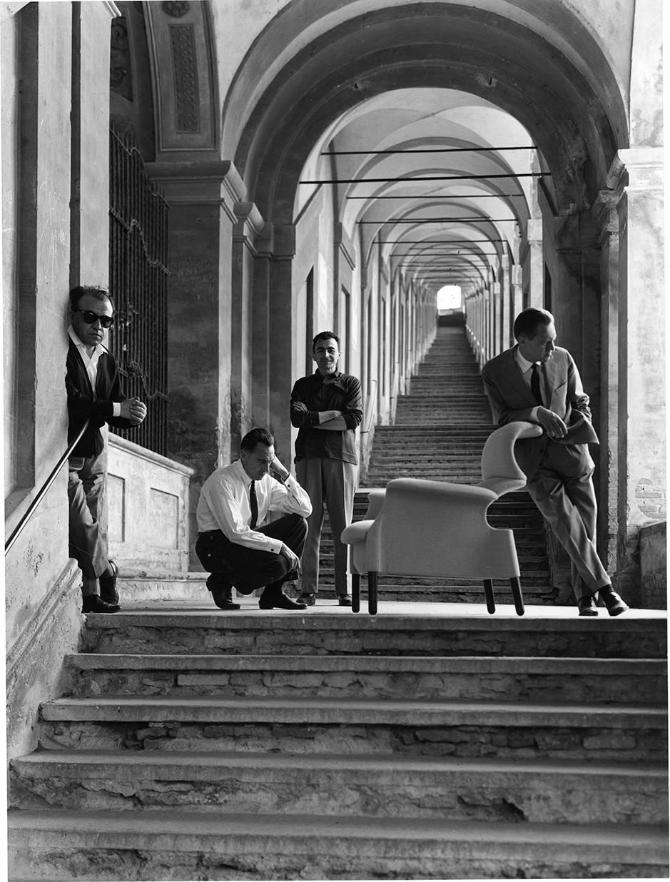 Dino Gavina, Achille e Pier Giacomo Castiglioni e Michele Provinciali fotografati accanto alla poltrona Sanluca sotto il portico di San Luca a Bologna, 1960 - Photo by Mauro Masera